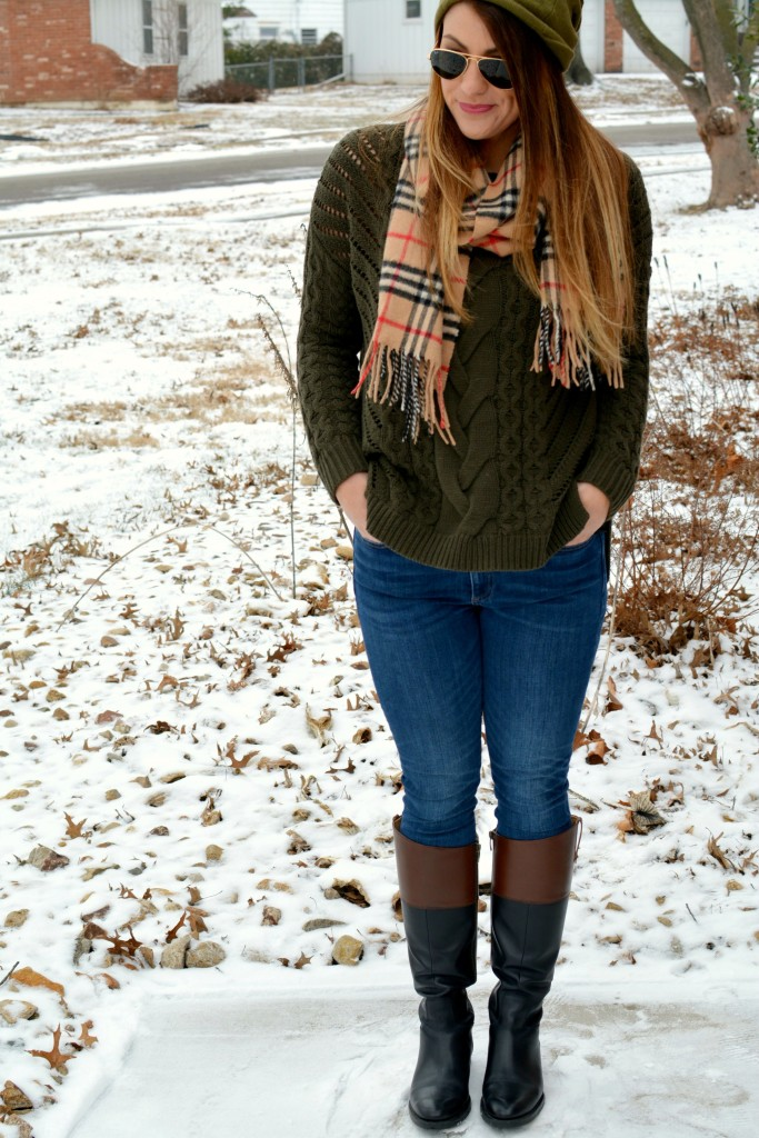 Ashley from LSR in an olive sweater, two-tone riding boots, a beanie, and a Burberry scarf
