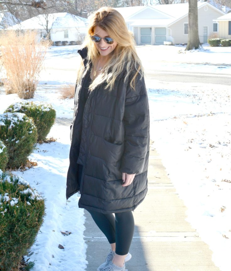 Ashley from LSR in an oversized parka, leggings, and sneakers
