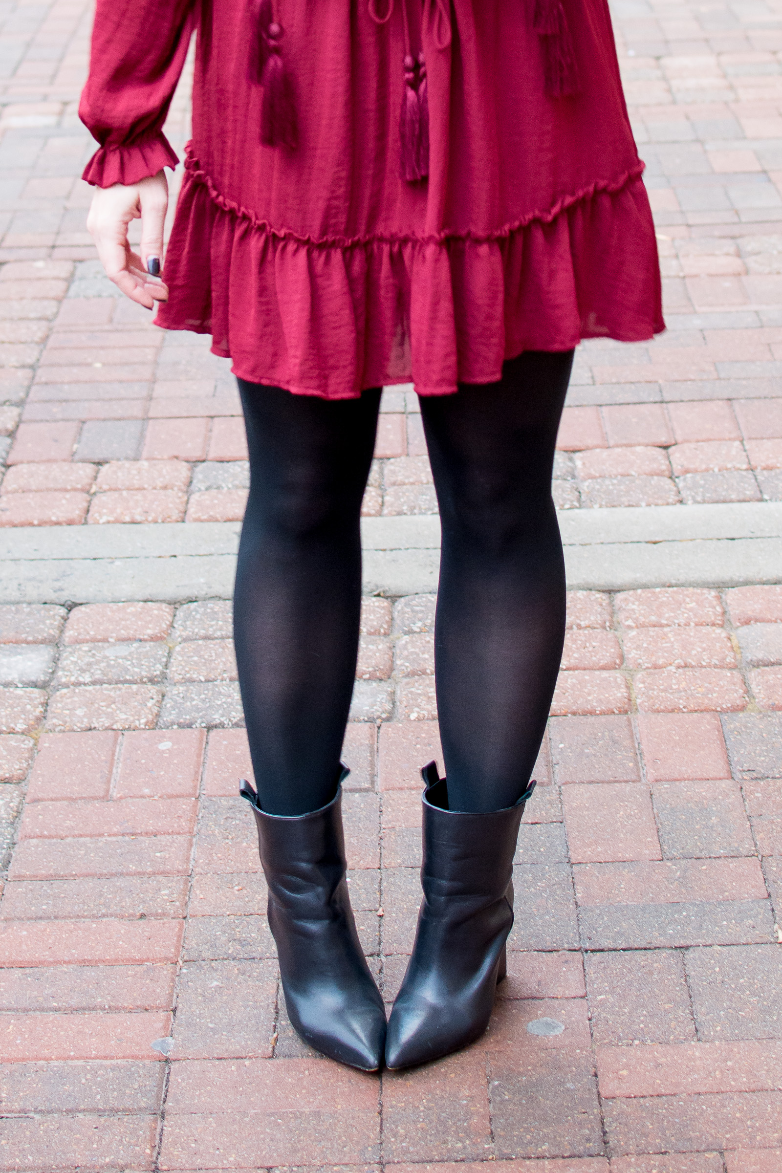 Ashley from LSR sharing a valentine's day outfit in a red dress, black tights, and black pointed toe boots