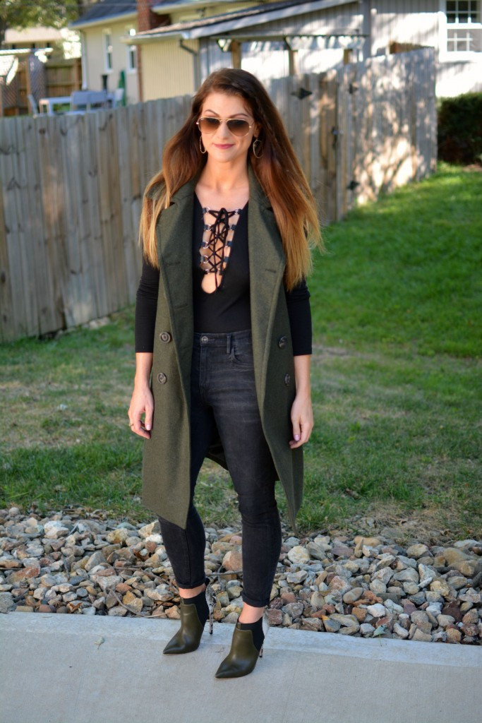 Ashley from LSR in a sleeveless military peacoat, a lace-up bodysuit, black Madewell jeans, and olive stiletto booties