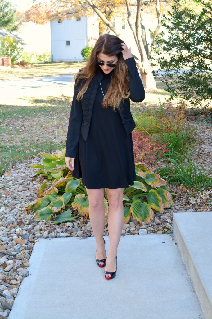 Ashley from LSR in a black turtleneck dress, black jacket, and Christian Louboutin pumps.
