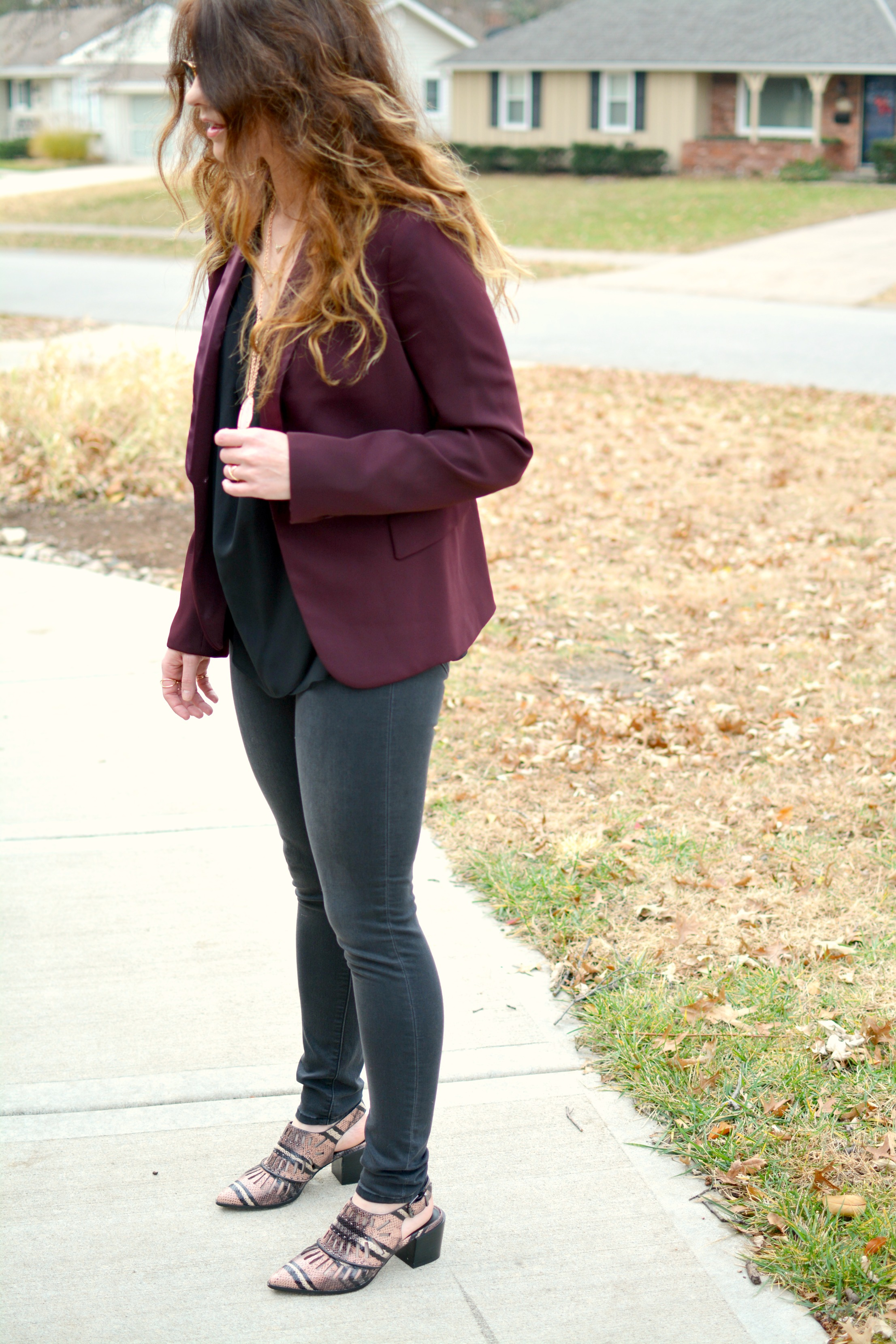Ashley from LSR in a burgundy blazer, black denim, and pink snakeskin ankle booties