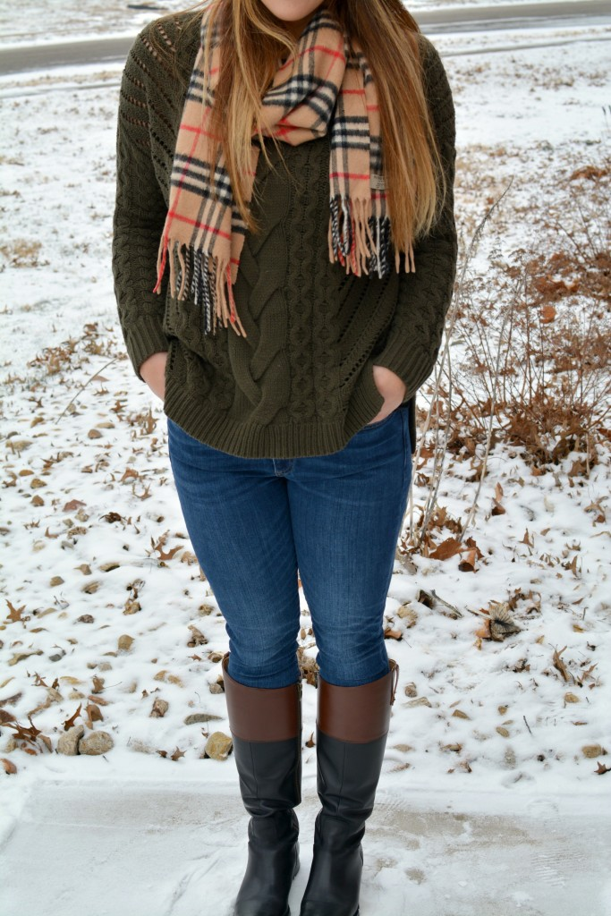 Ashley from LSR in an olive sweater, two-tone riding boots, and a Burberry scarf