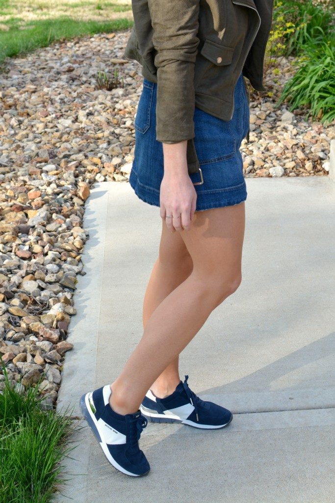 Ashley from LSR in an overall dress, suede jacket, and retro sneakers