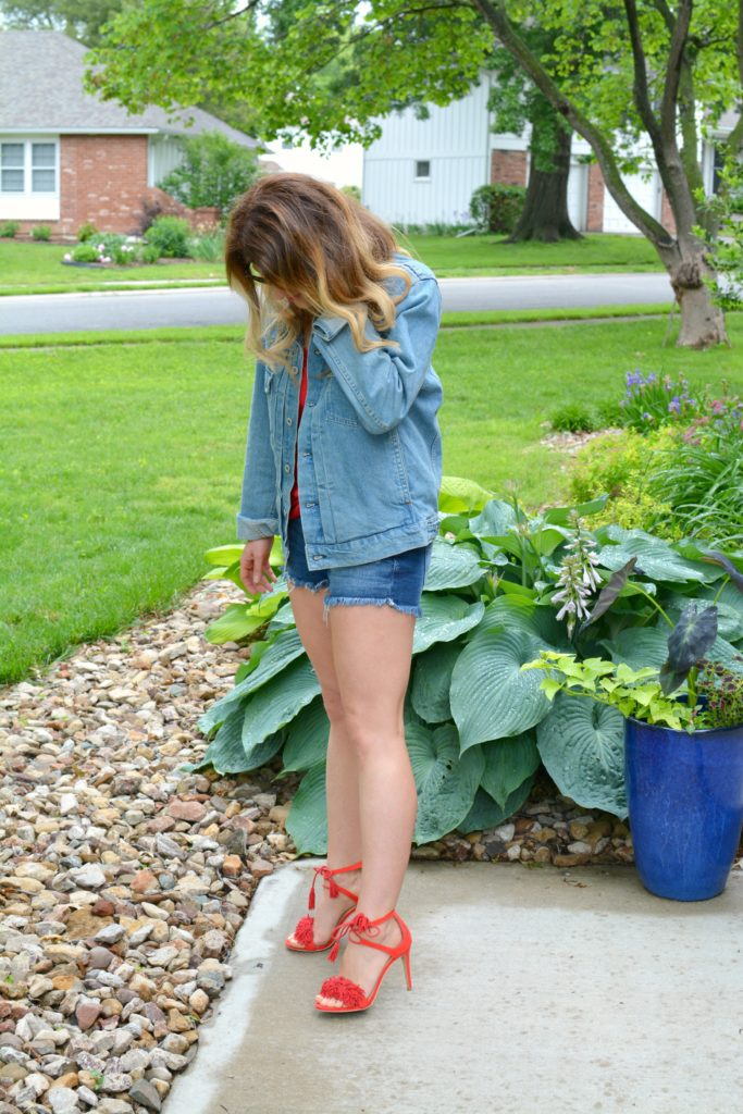 Ashley from LSR in a men's denim jacket, cutoff shorts, and red fringe sandals