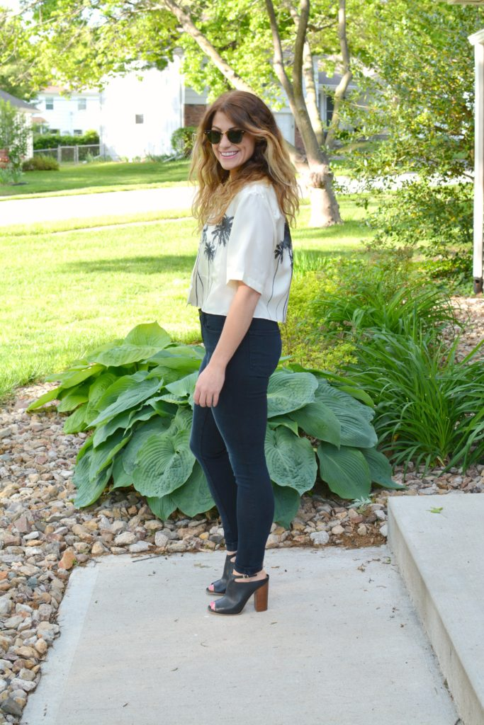 Ashley from LSR in a palm tree crop top, Frame jeans, and black mules