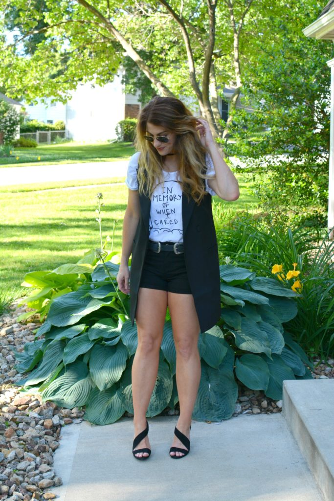 Ashley from LSR in a Sex & Ice Cream tee, long black vest, and black sandals