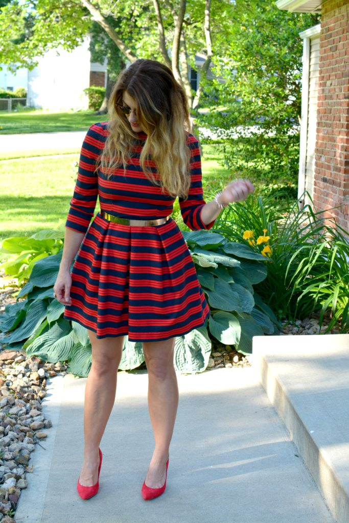 Ashley from LSR wearing a red and blue striped dress, red pumps, and metal belt