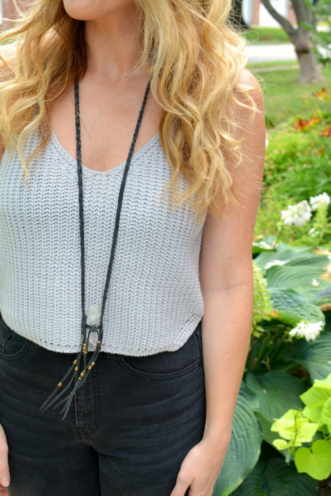 Ashley from LSR in a gray cropped sweater tank and clear quartz necklace