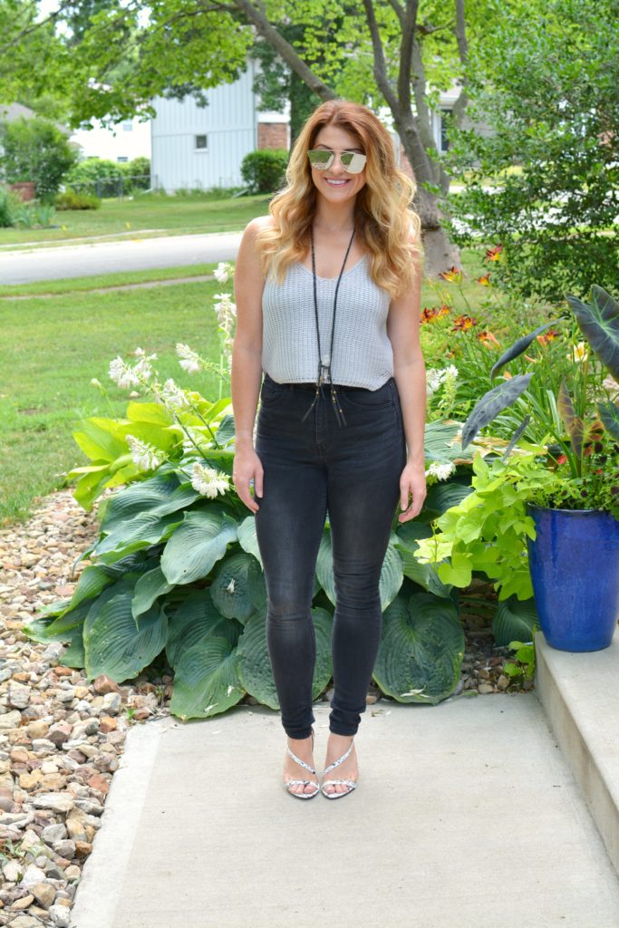 Ashley from LSR in a cropped gray sweater tank, black jeans, and white marble sandals
