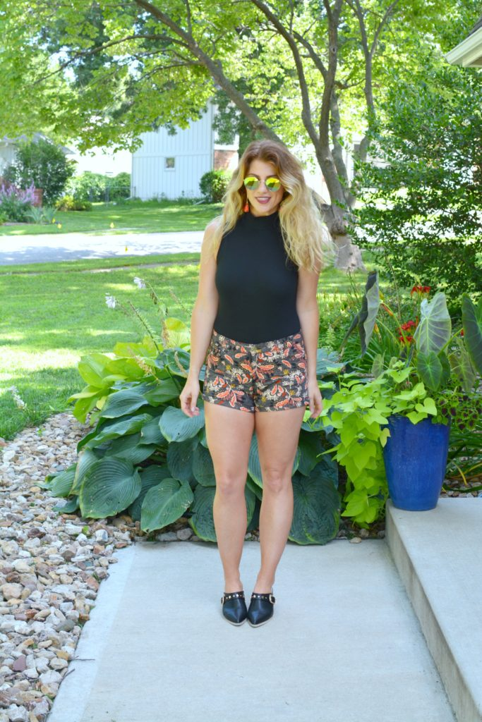 Ashley from LSR In a black bodysuit, printed shorts, and black leather mules
