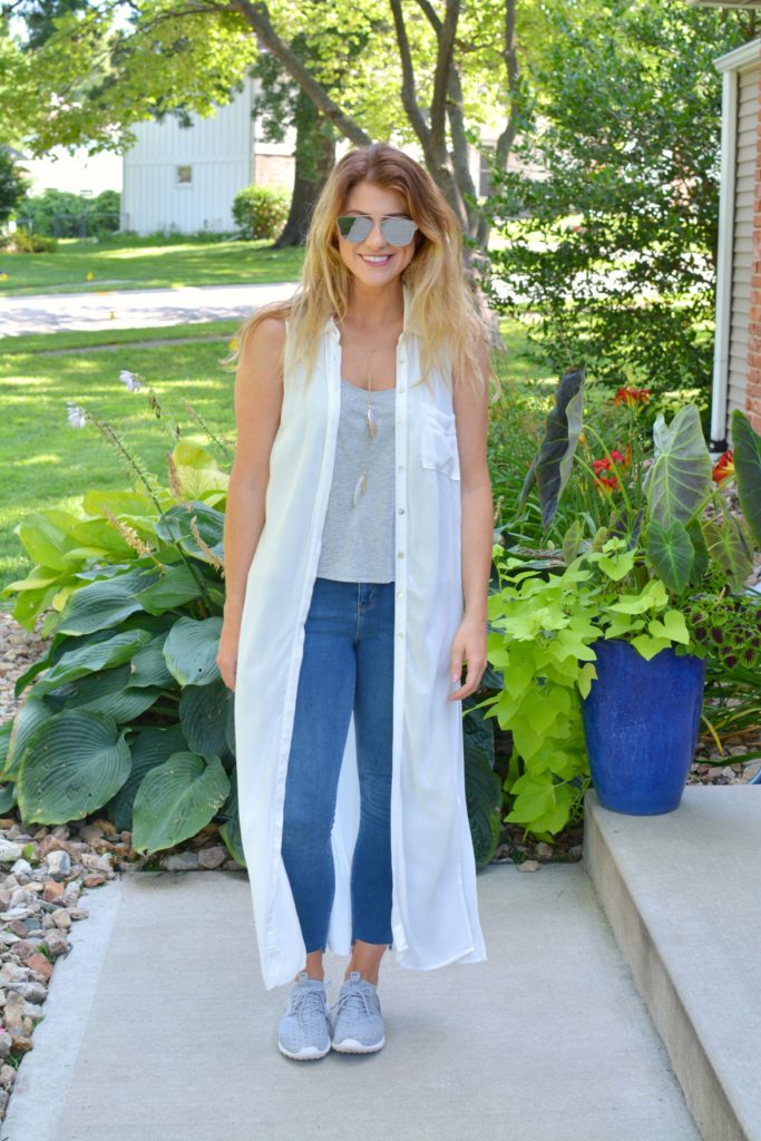 Ashley from LSR in a white duster, stepped hem jeans, and gray Nike's