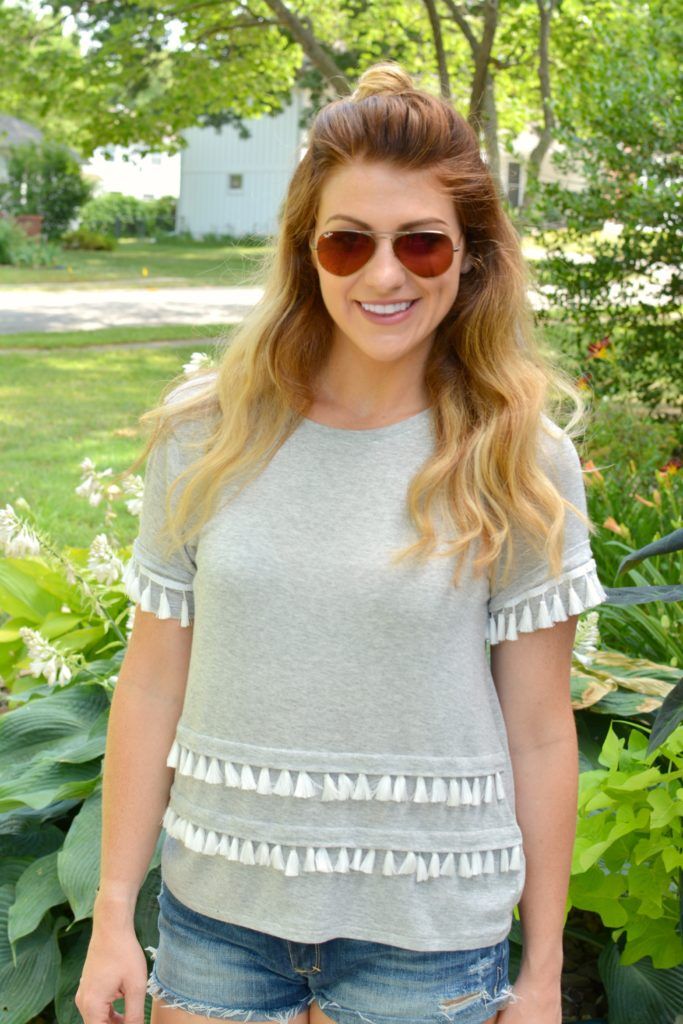 Ashley from LSR in a gray tassel tee and cutoff shorts