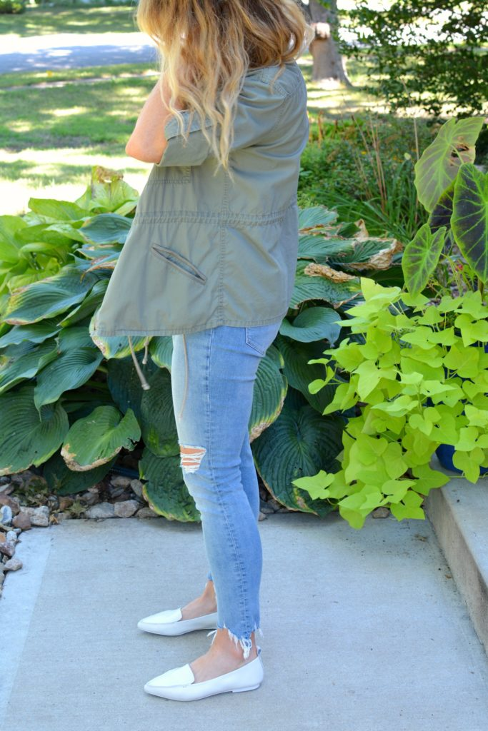 Ashley from LSR in an olive green utility jacket, destroyed denim, and white loafers