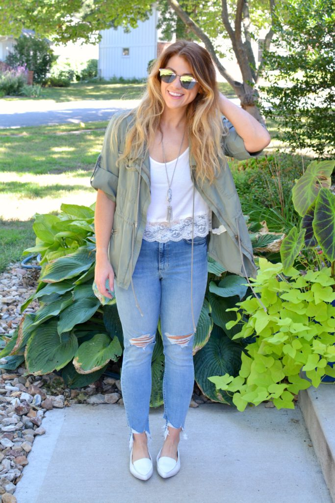 Ashley from LSR in an olive green utility jacket, destroyed denim, white loafers, and Fendi sunglasses