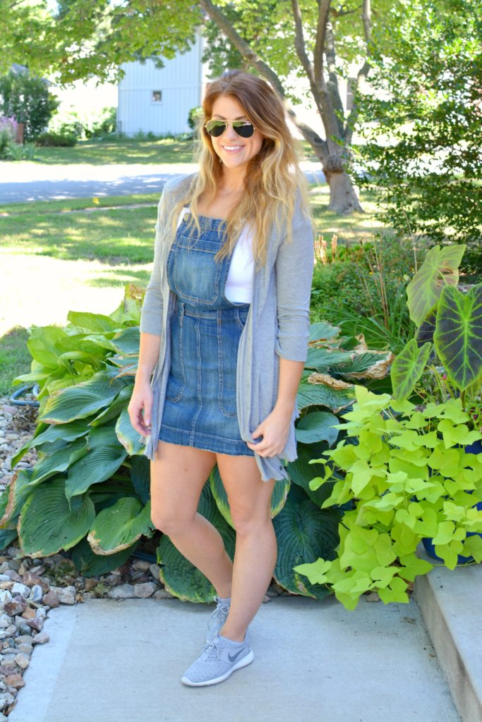 Ashley from LSR in an overall dress, gray cardigan, and gray Nike Juvenate sneakers