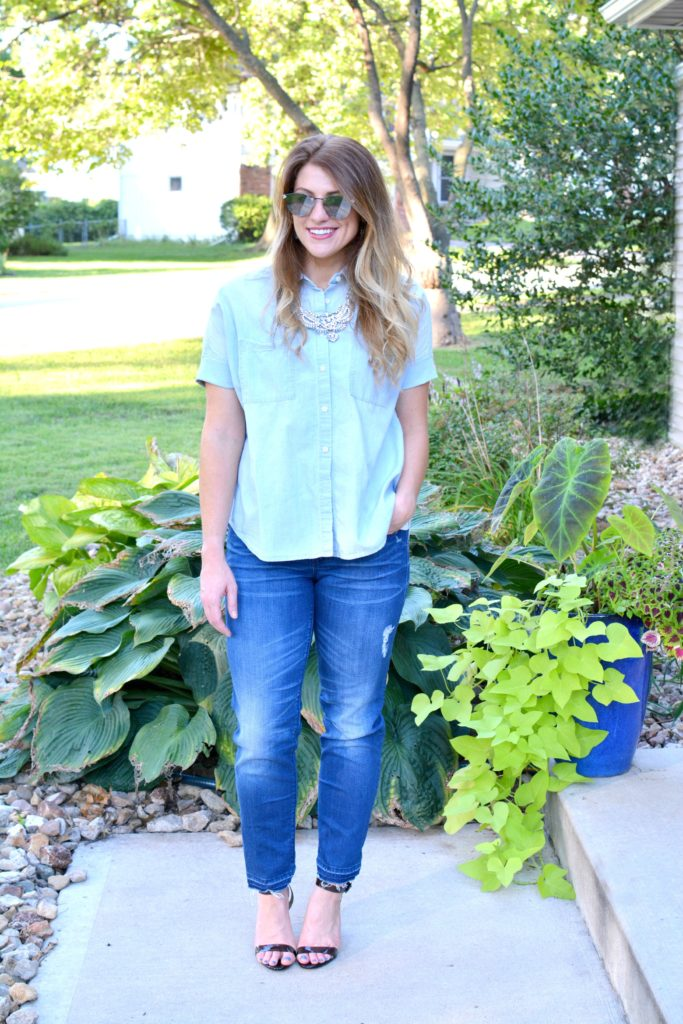 Ashley from LSR in a light chambray shirt, raw hem jeans, and lucite heels with a statement necklace