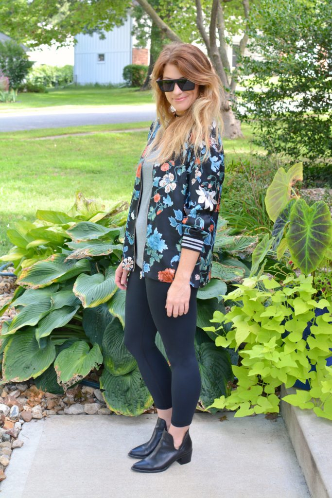Ashley from LSR wearing a floral bomber jacket from H&M with black leggings and ankle boots