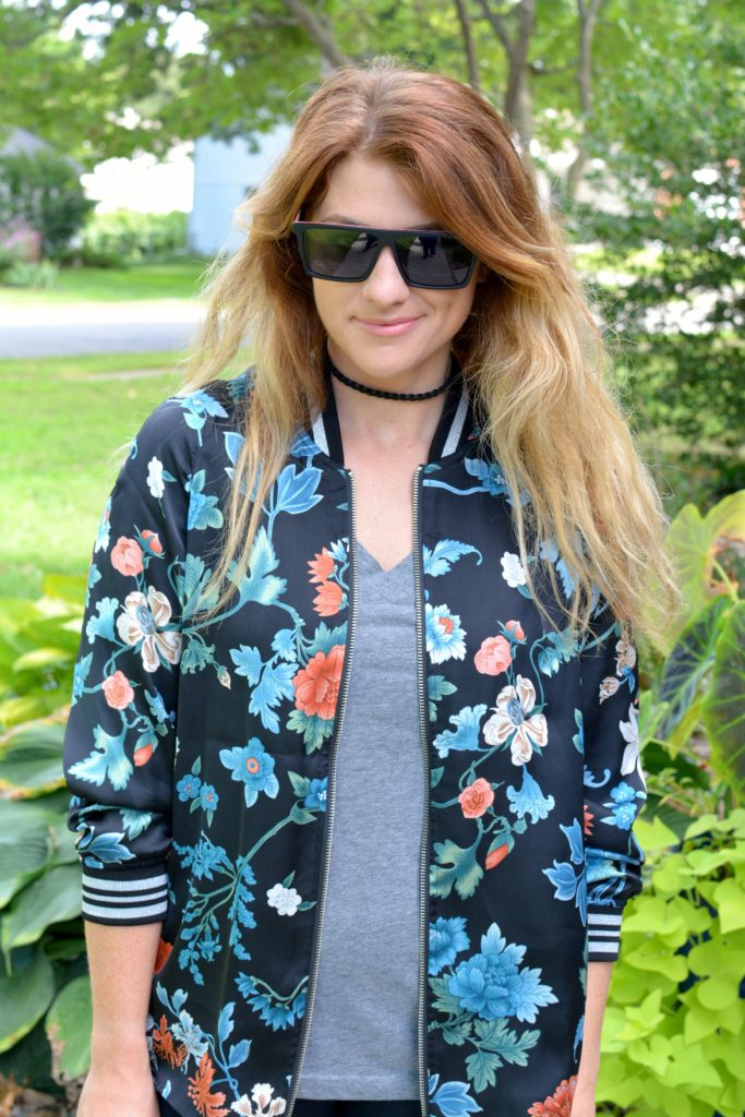 Ashley from LSR wearing a floral bomber jacket from H&M with a gray t-shirt and Proof sunglasses