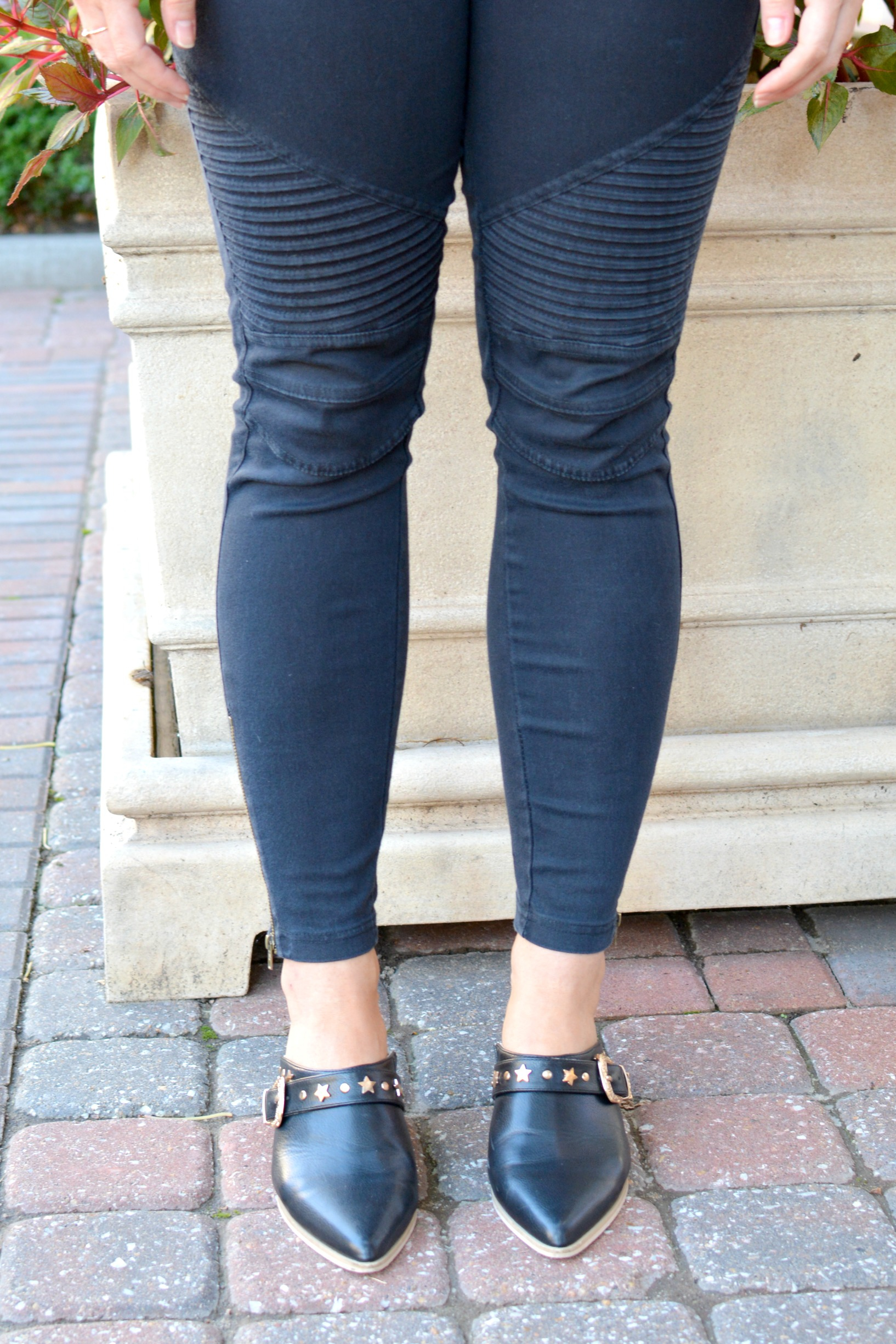 Ashley from LSR in black moto leggings and leather mules.