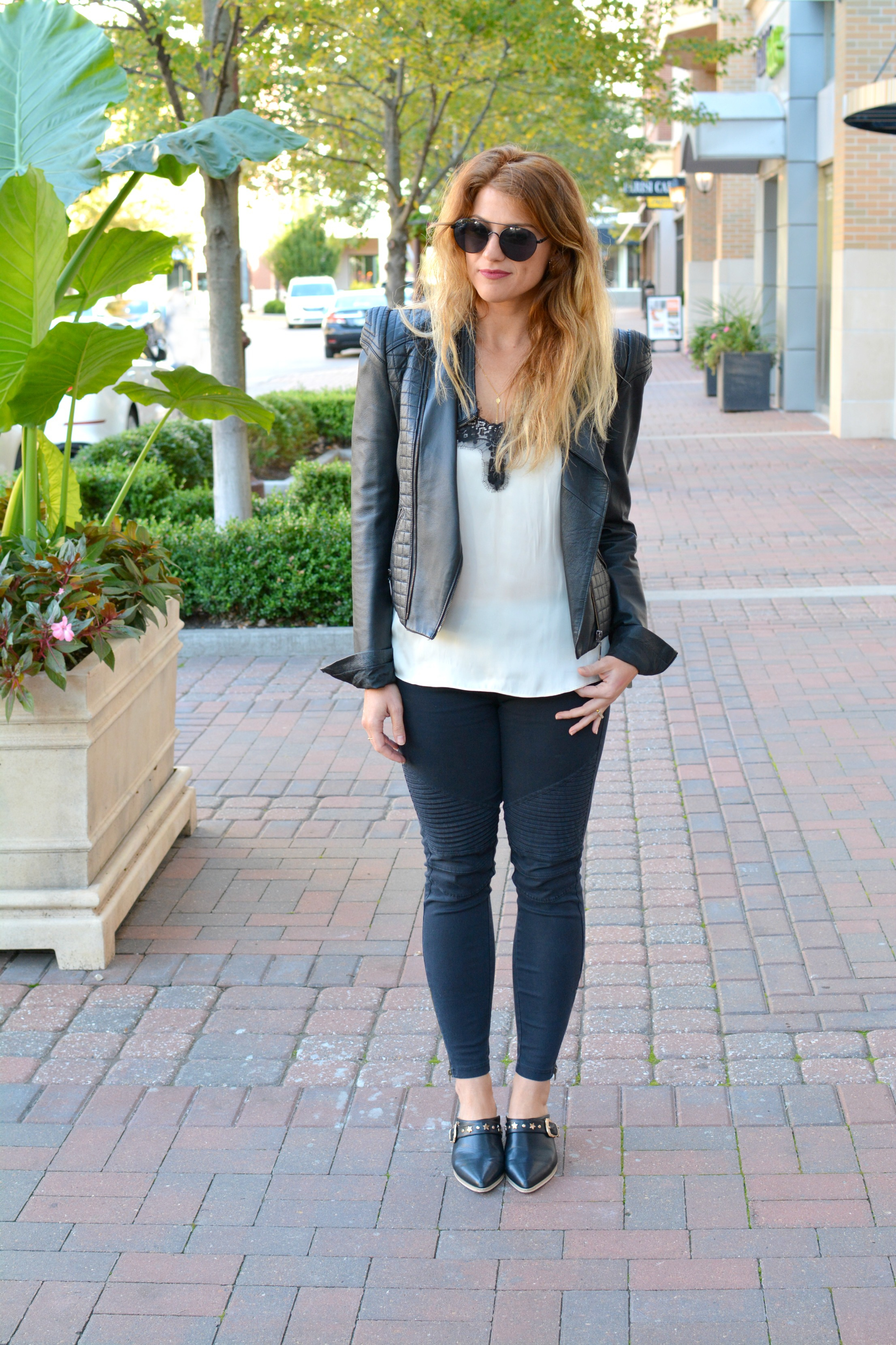 Ashley from LSR in a cream satin and black lace tank, black moto leggings, and a leather jacket