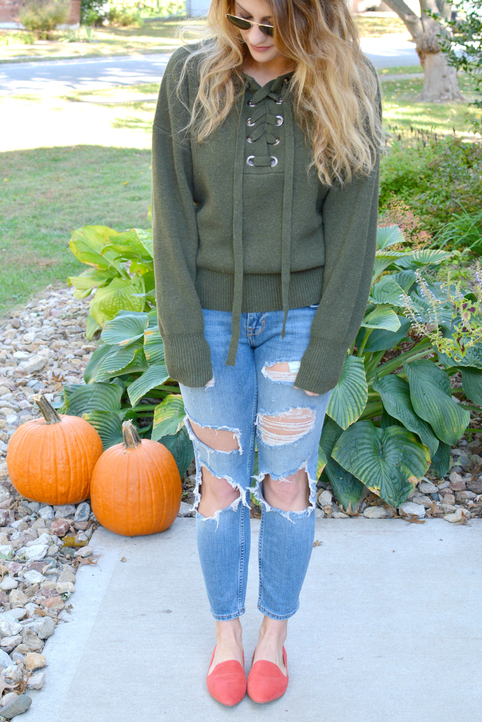 Ashley from LSR in a green lace-up sweater, destroyed denim, and orange flats