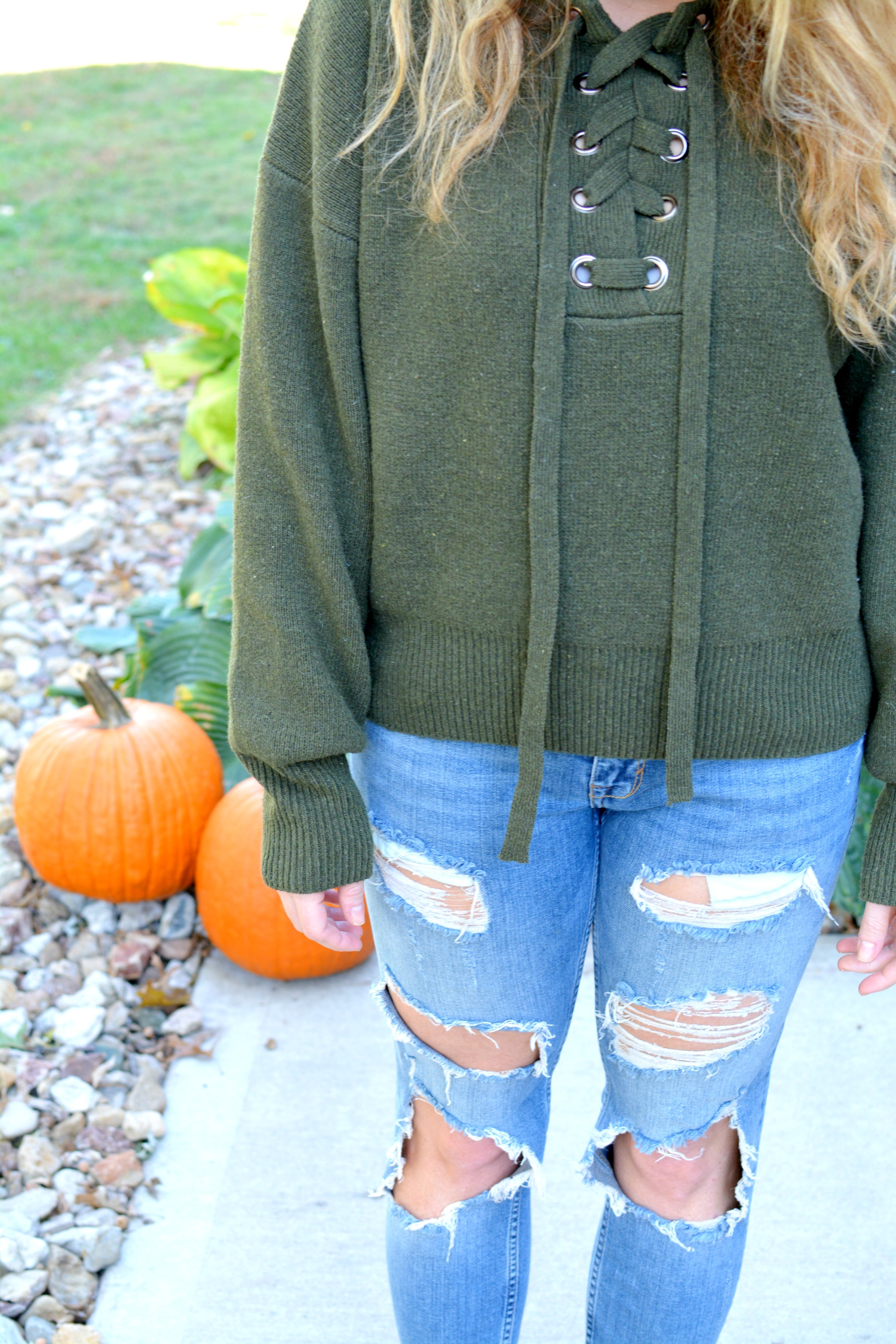 Ashley from LSR in a green lace-up sweater and destroyed denim