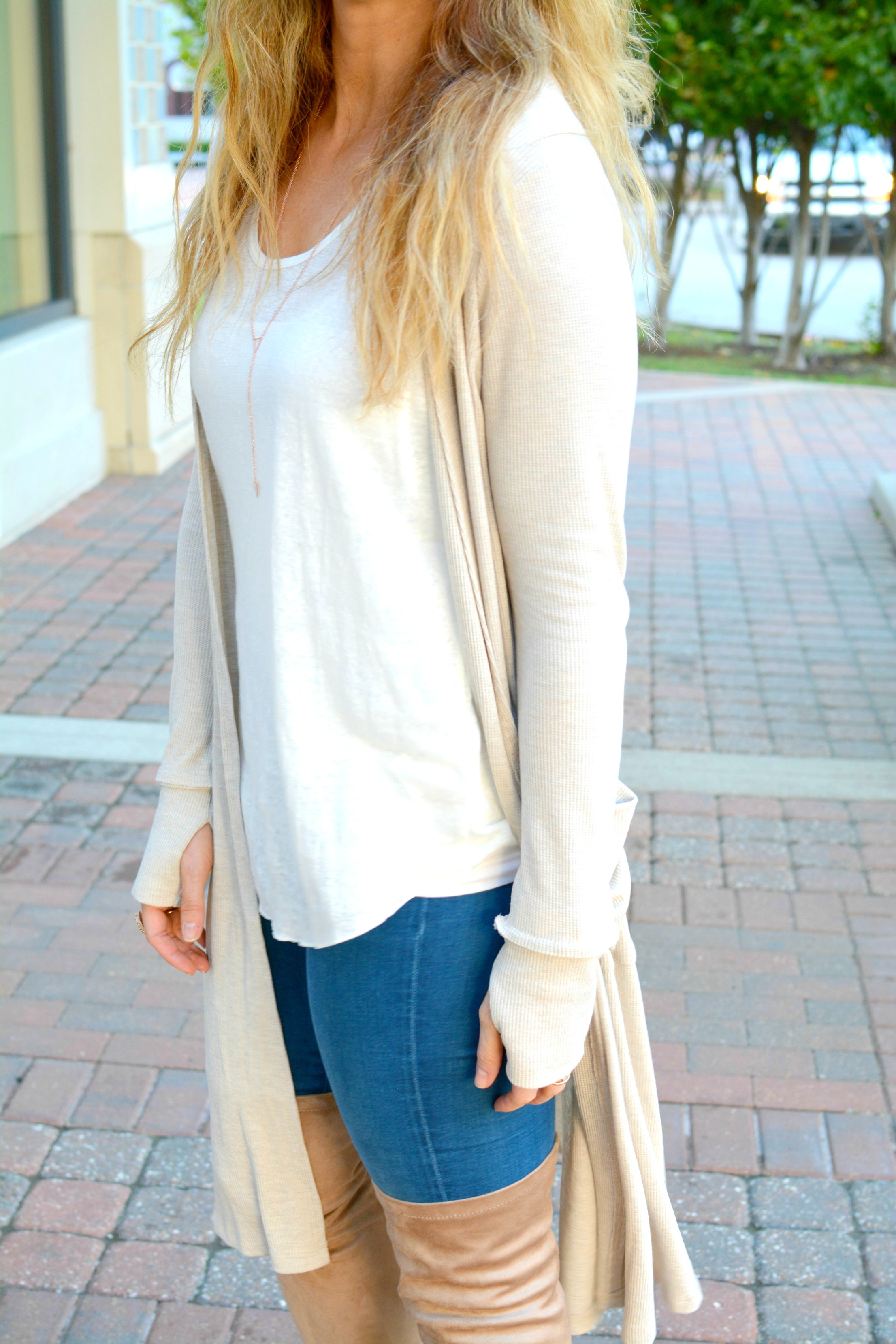 Ashley from LSR in a beige long cardigan and nude thigh high boots
