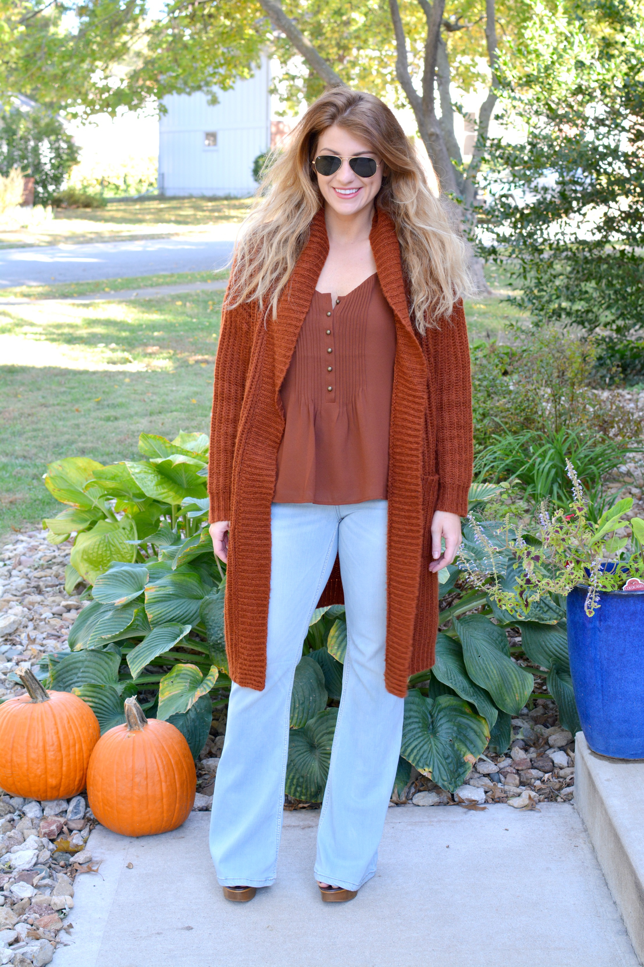 Ashley from LSR in a rust camisole, rust cardigan, and light wash flares