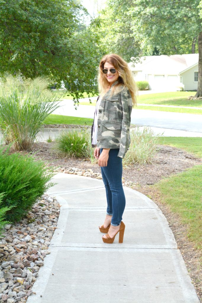 Ashley from LSR in a camo jacket, striped tank, and platform sandals