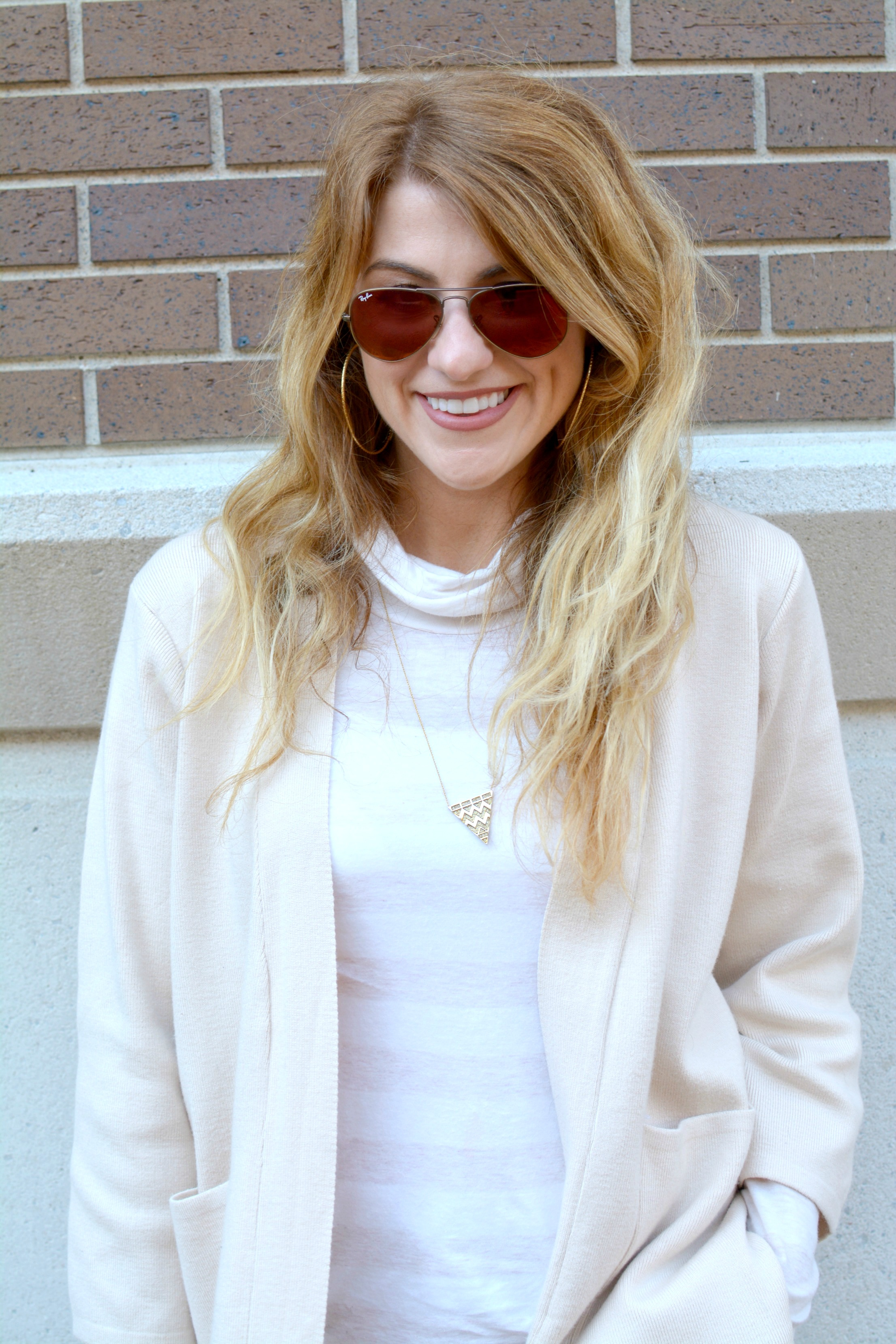 Ashley from LSR in a beige cardigan and red Ray-Ban sunglasses