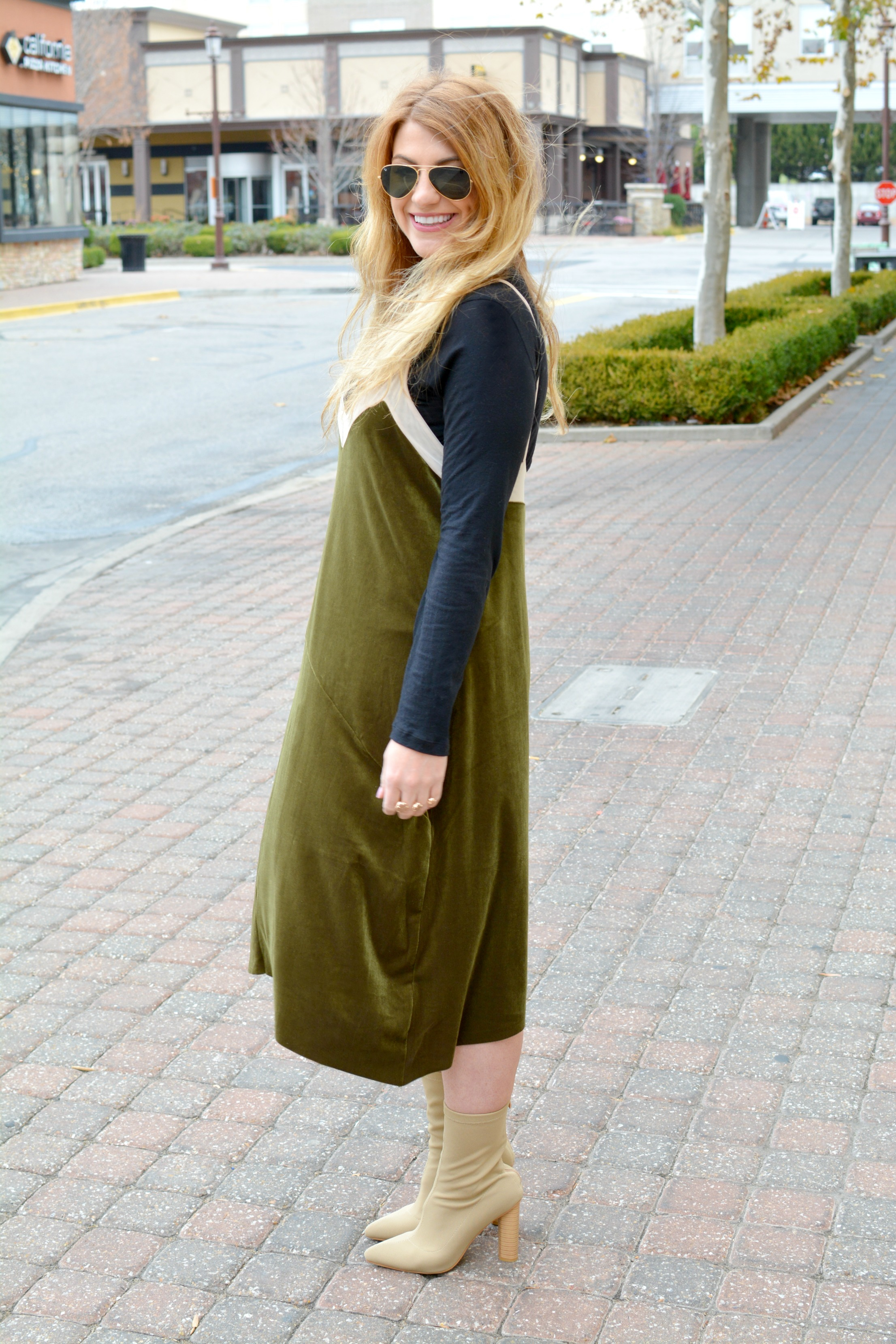 Ashley from LSR in a green velvet dress and sock boots