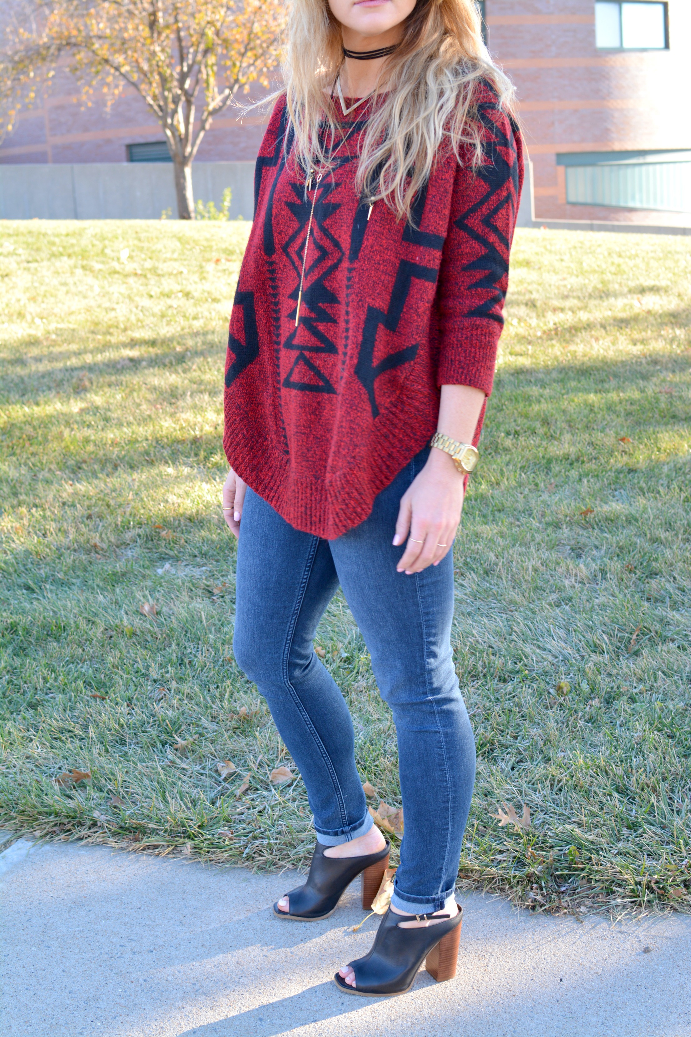 Ashley from LSR in a red and black sweater with leather mules