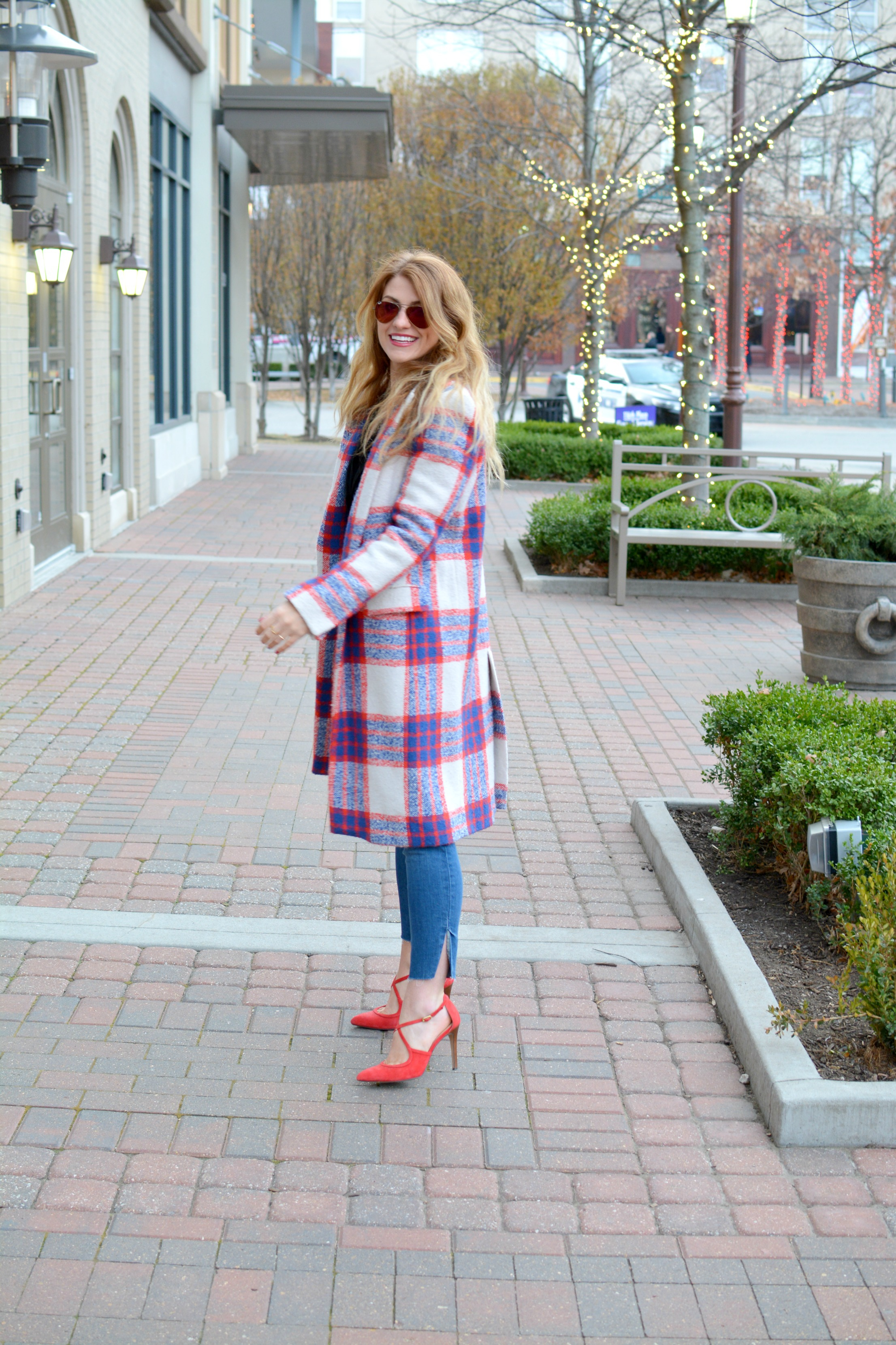 Ashley from LSR in a plaid statement coat and red pumps