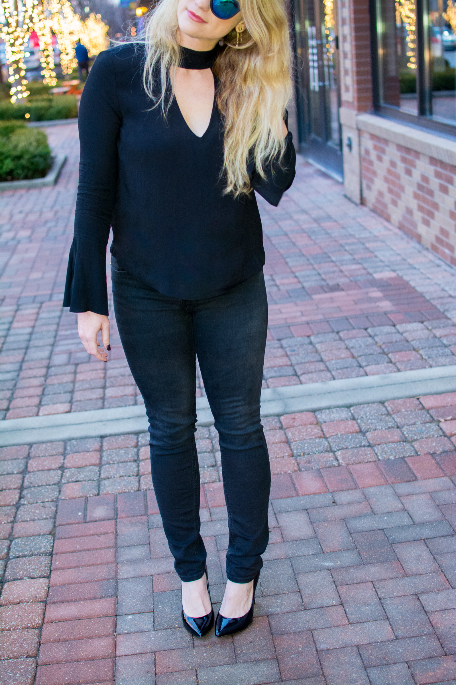 Ashley from LSR In a black choker blouse, black denim, and black pumps