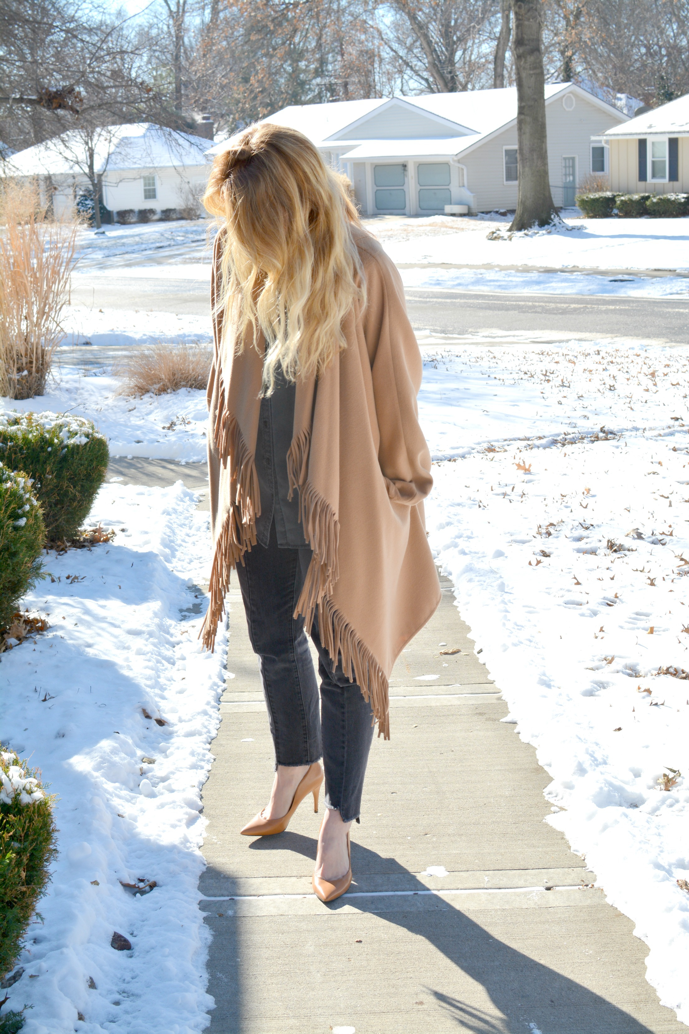 Ashley from LSR in a fringe camel coat, camel pumps, and dark stepped-hem denim