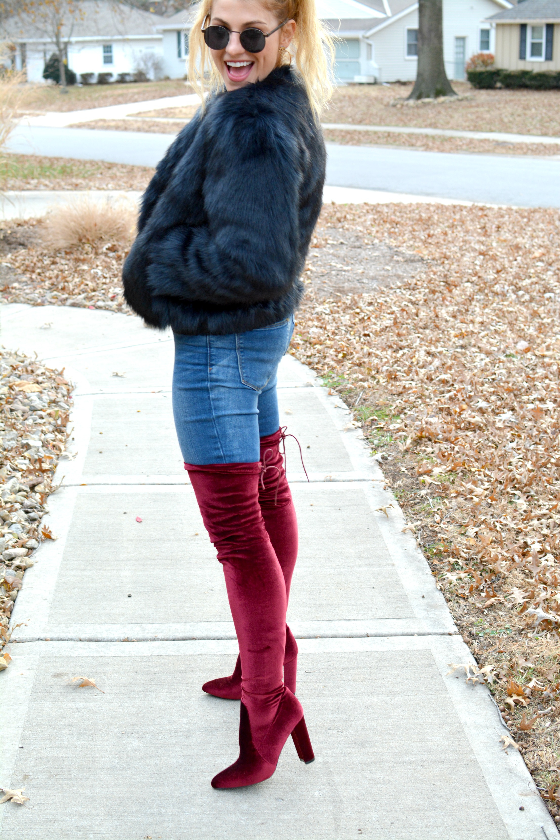 Ashley from LSR in a navy faux fur jacket and burgundy thigh high boots