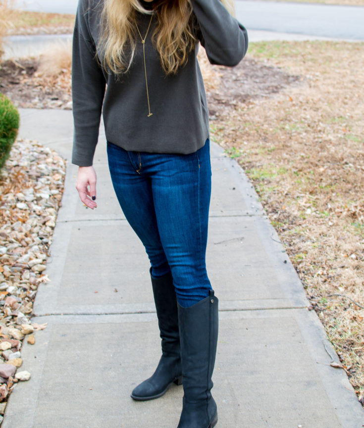 Ashley from LSR in an olive green sweater, basic skinny jeans, and black riding boots