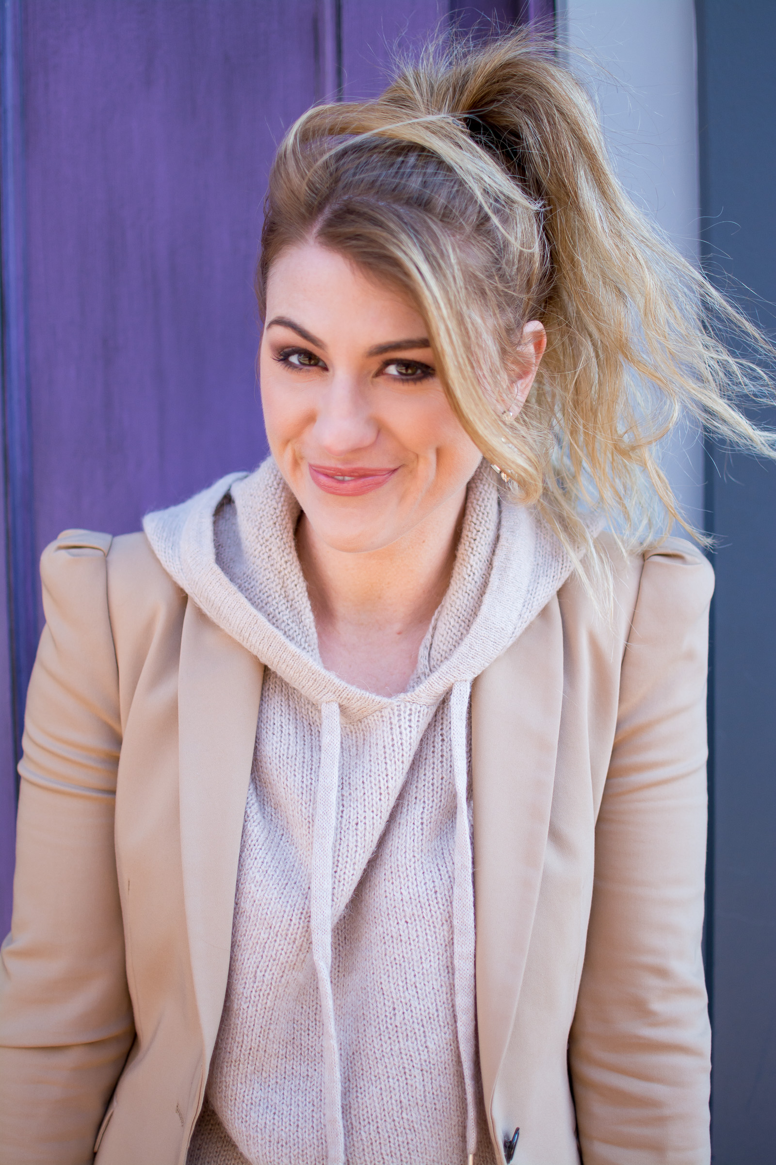 Ashley from LSR in a camel blazer and blush hoodie