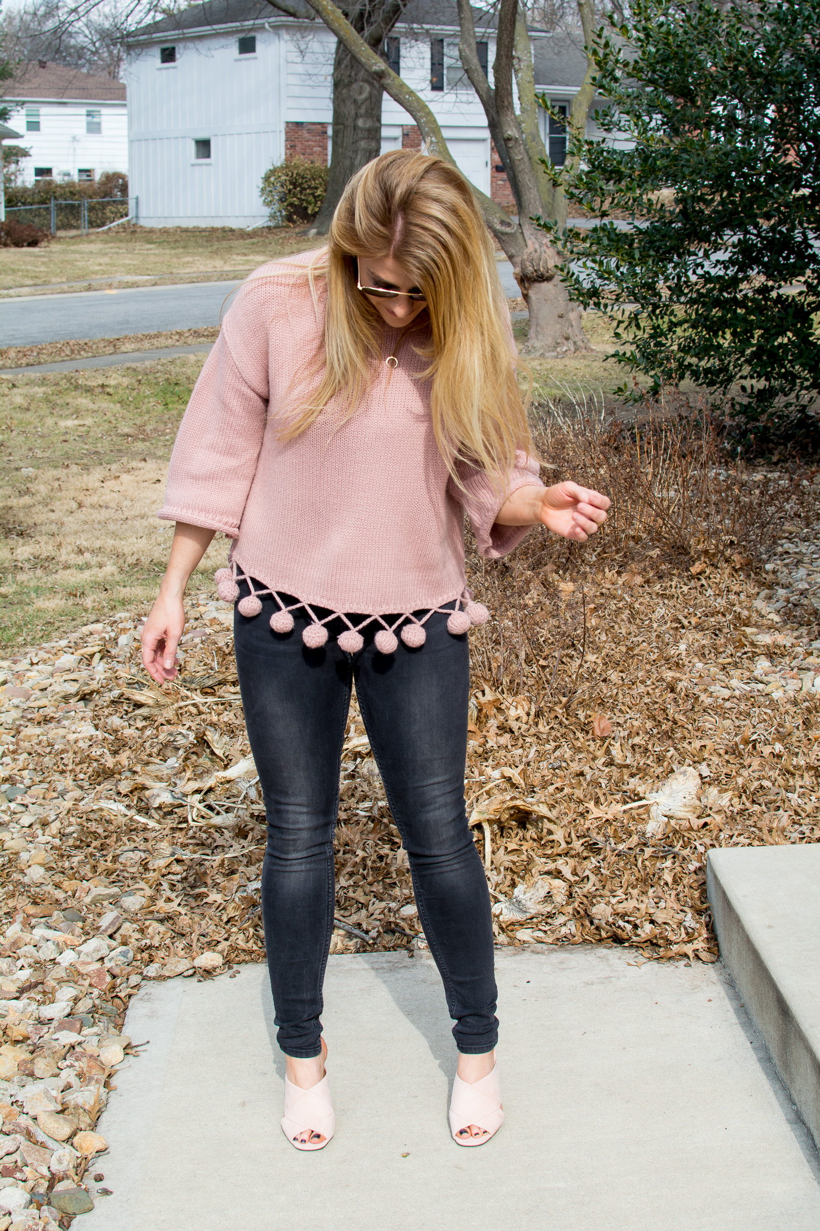 Ashley from LSR in a pink pom pom sweater with black denim and pale pink suede mule sandals
