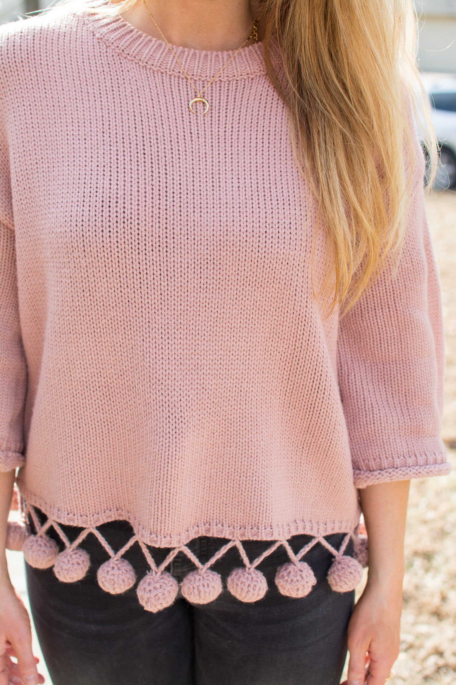 Ashley from LSR in a pink pom pom sweater with black denim