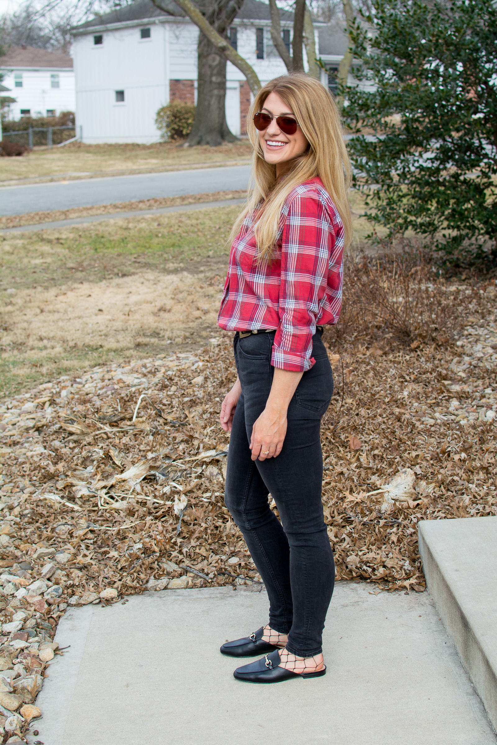 Ashley from LSR in a red Madewell shirt, black jeans, loafer mules, and fishnets