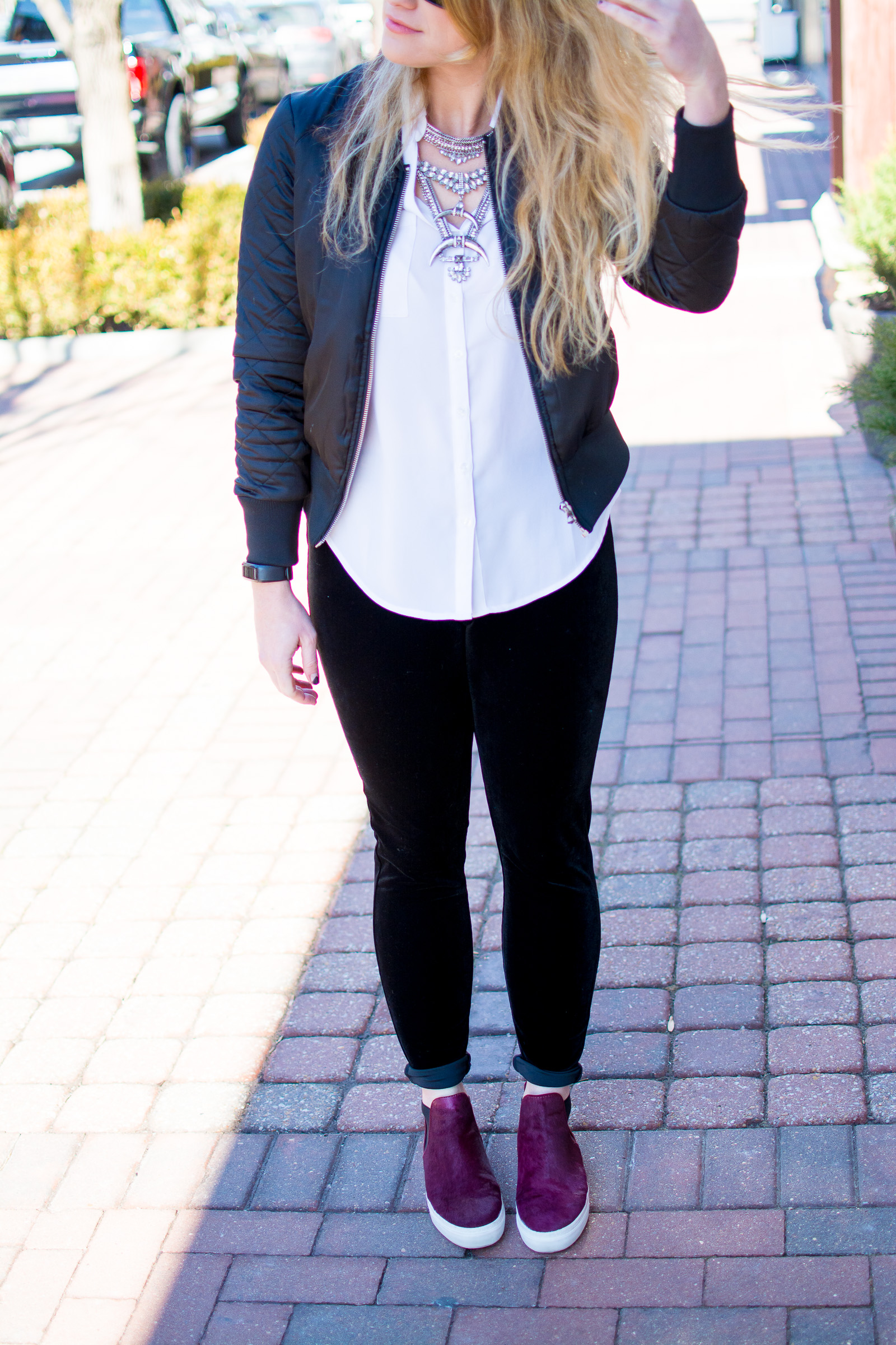 Ashley from LSR in velvet leggings, a satin bomber jacket, sneakers, and a statement necklace for a casual valentine's day outfit