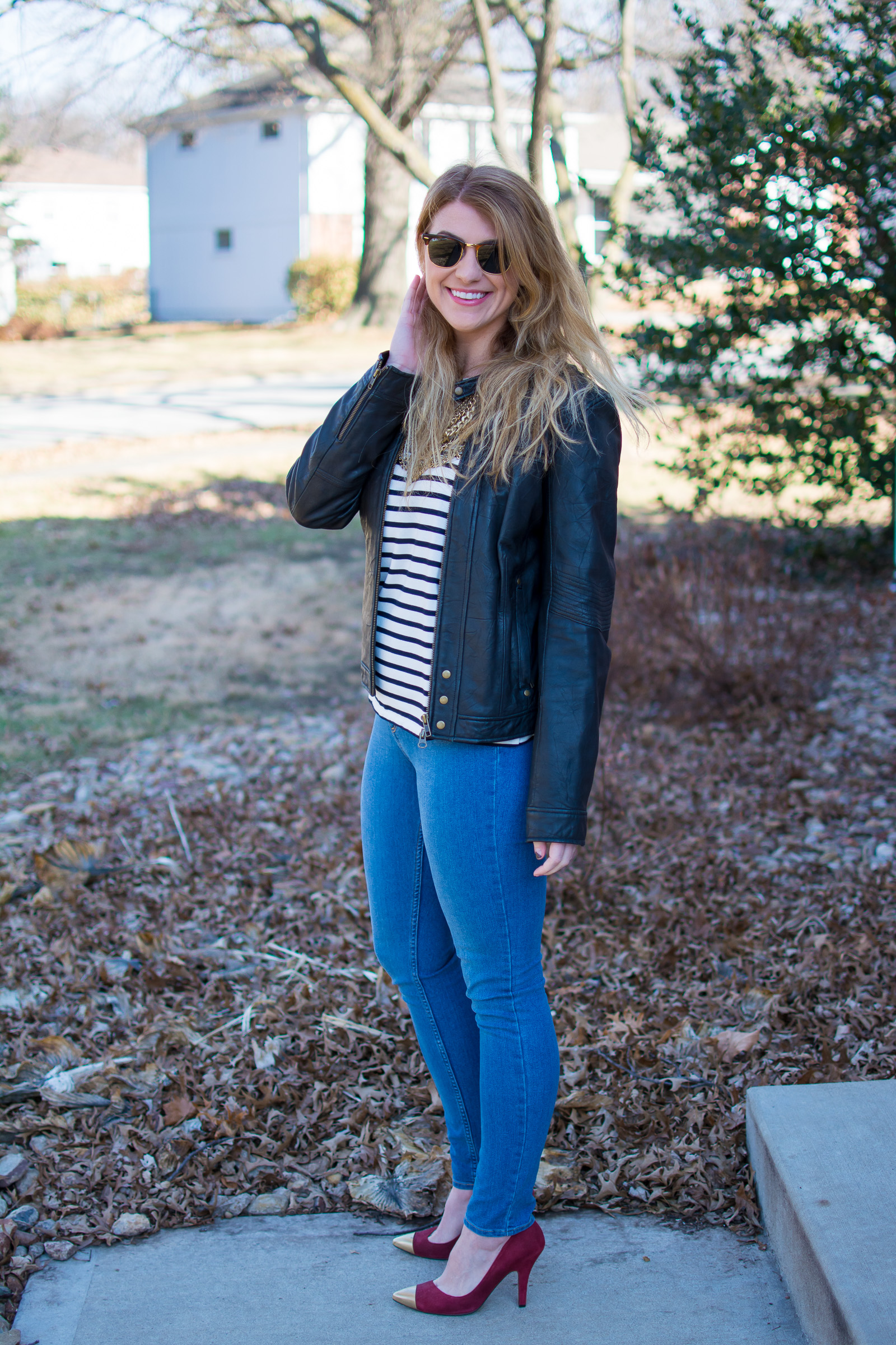 Ashley from LSR in a stripe t-shirt, leather jacket, and gold cap toe suede pumps
