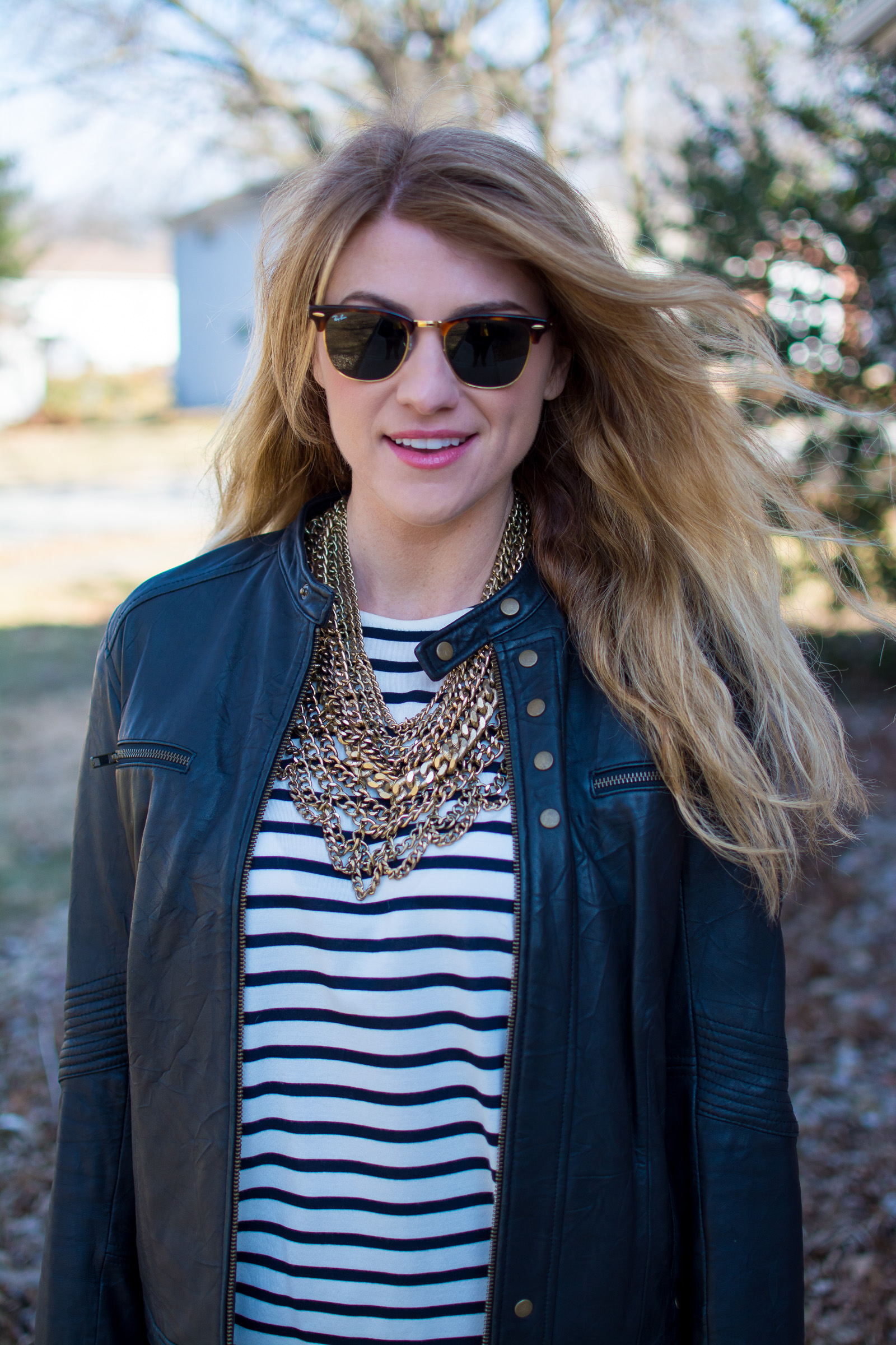 Ashley from LSR in a stripe t-shirt, leather jacket, and gold chain statement necklace